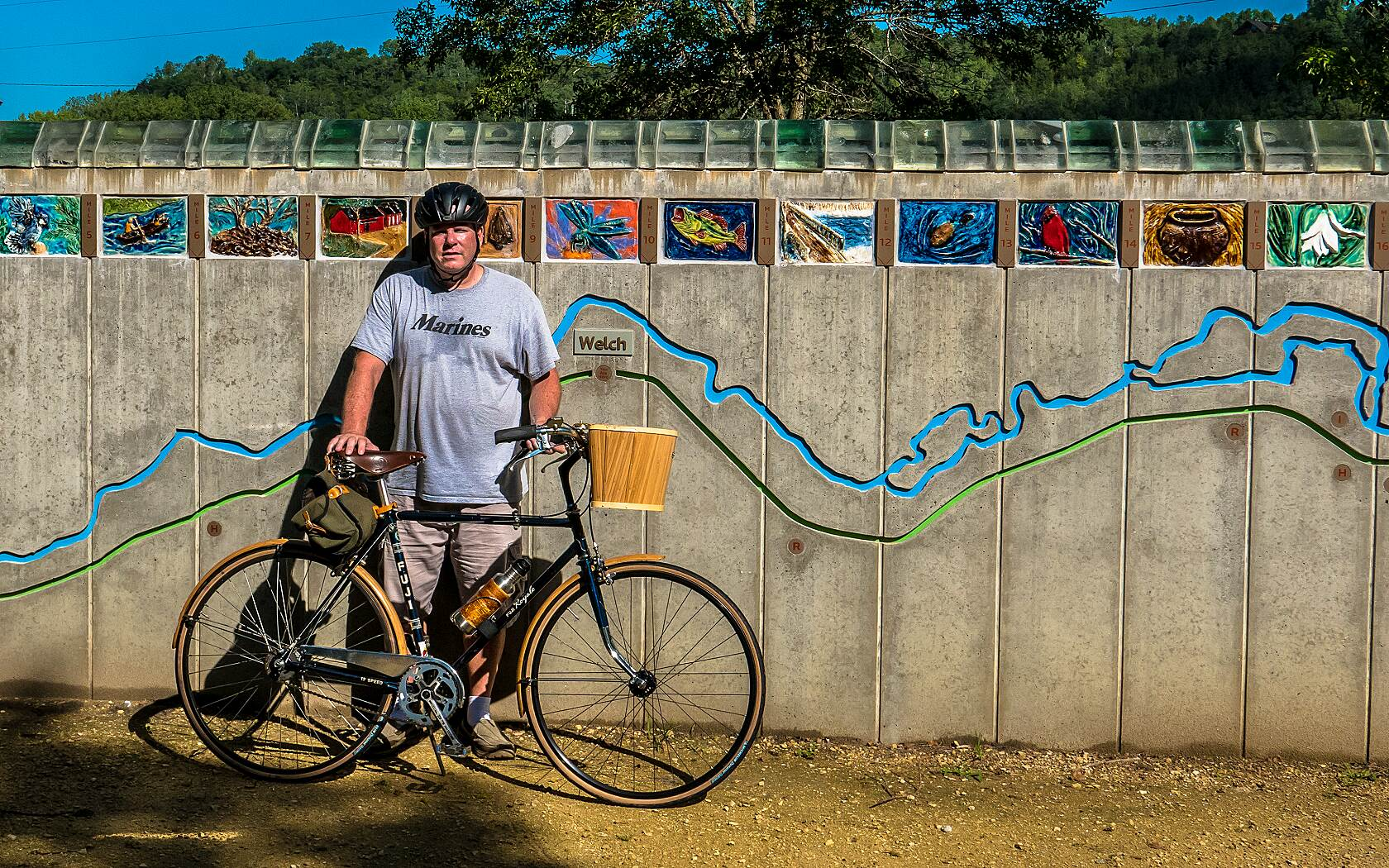 Cannon Valley Trail One Happy Marine One of the trail attendants at Welch Station was kind enough to take this photo of me with my bike in front of the beautiful 'map wall' display.