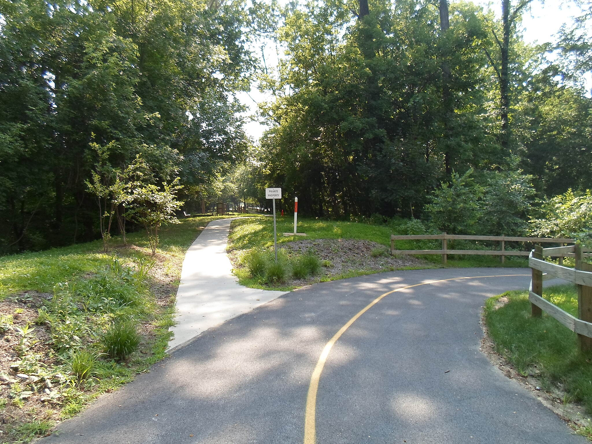 Chester Valley Trail Chester Valley Trail Trail junction immediately west of the Cedar Hollow Road crossing; the trail curves sharply right, while the sidewalk heads straight into the Vanguard Corporate Center. Taken July 2015.