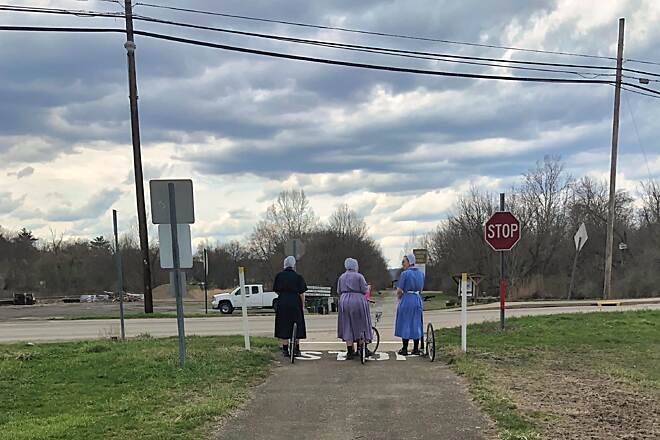 Conotton Creek Trail Amish Scooter Riders A trio of Amish women stop at a road crossing along the trail.  These ladies used their scooters to traverse the route.  April 2019.
