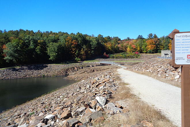 Grand Trunk Trail View along Westville Dam View northward along trail descending along upstream face of Westville Dam on 10/10/16. In the background is the bridge over the spillway and then the trail going to the left (west) along the woods.