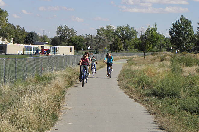 High Line Canal Trail (CO) School kids ride home on the trail Next to South Middle School in Aurora.