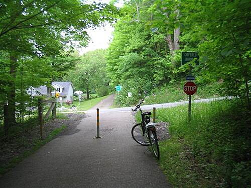 Little Beaver Creek Greenway Trail MP5 - road to covered bridge MP5 - Road to covered bridge. Note how sign is almost obscured by trees.
