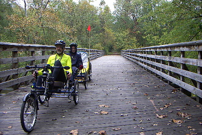 Lower Trail Trai l Bridge Penninger recumbent trike tandem & trailer crossing the river. October 2005