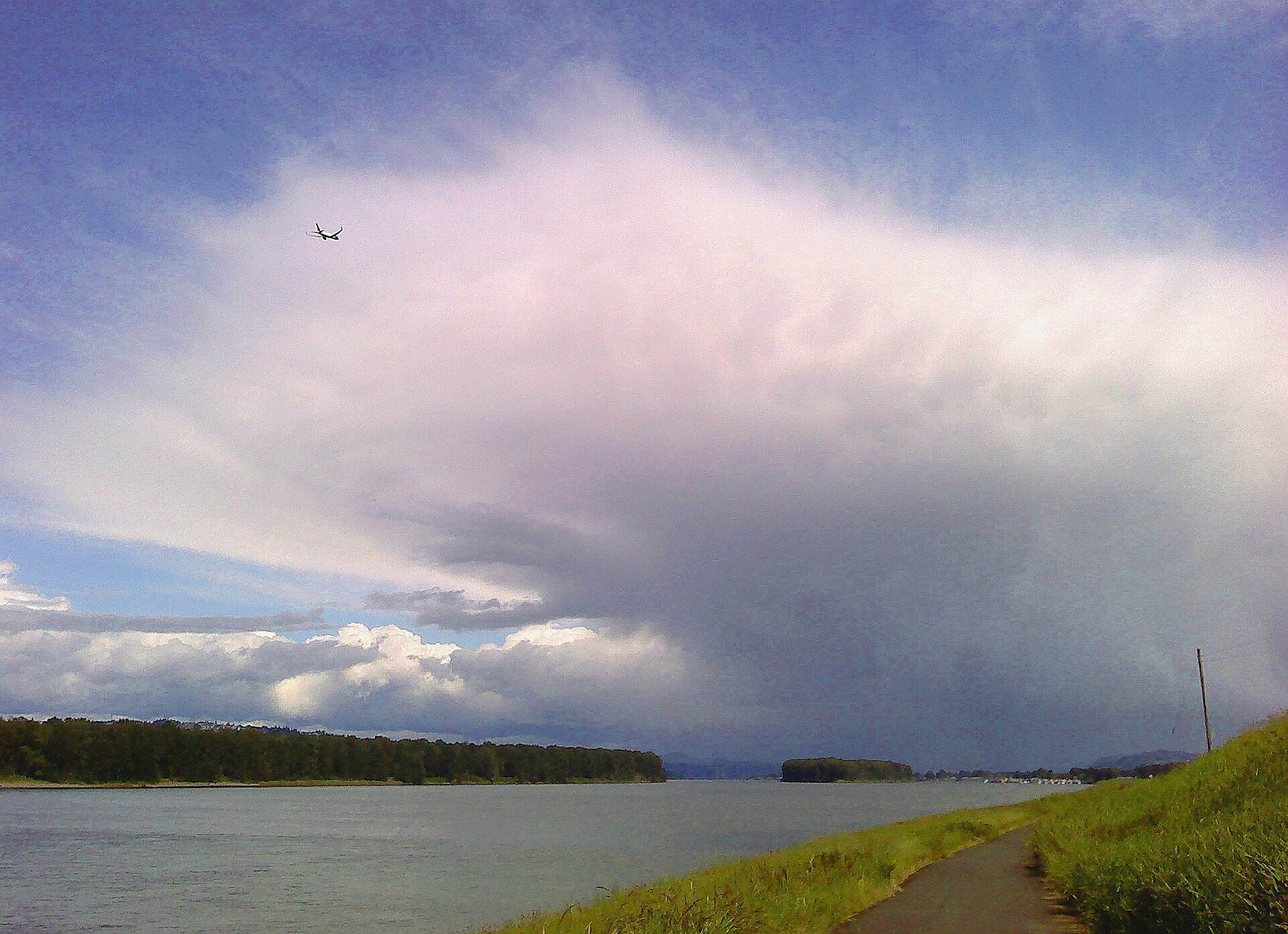 Marine Drive Trail along the Marine Drive trail nice clouds and airplane above, Columbia River and Marine Drive bike path below. Just east of the Portland Airport.