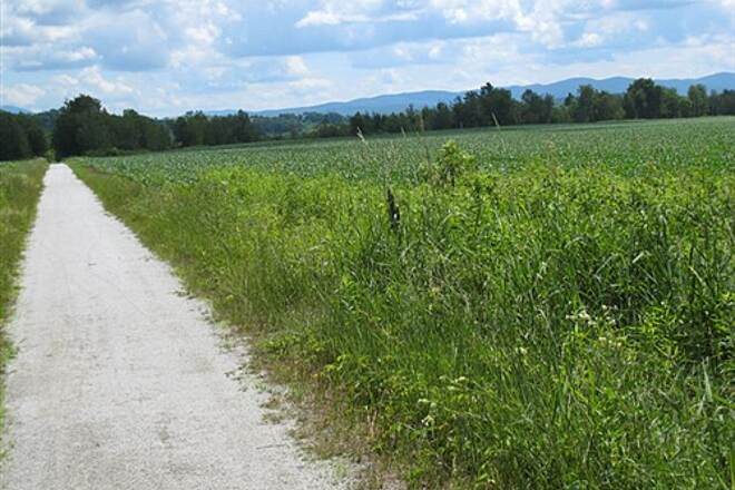 Missisquoi Valley Rail-Trail Hills in distance Open trail with typical view of mountains