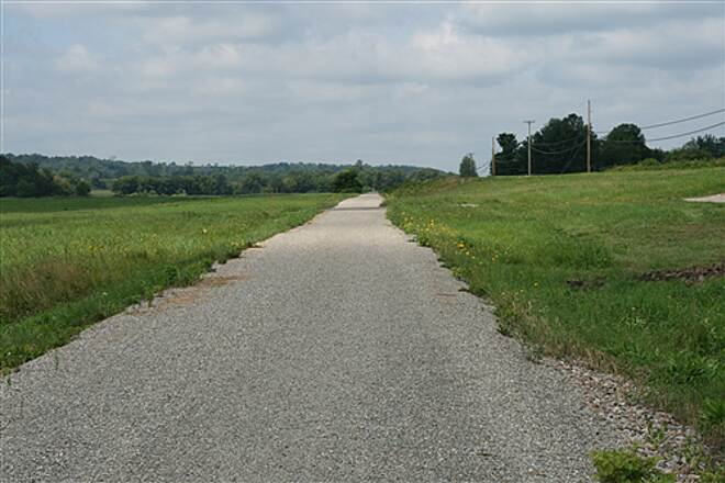 Missisquoi Valley Rail-Trail  Much of the trail cuts through wide meadows and pasture.  This is outside of Enosburg.  Route 105 is at right.