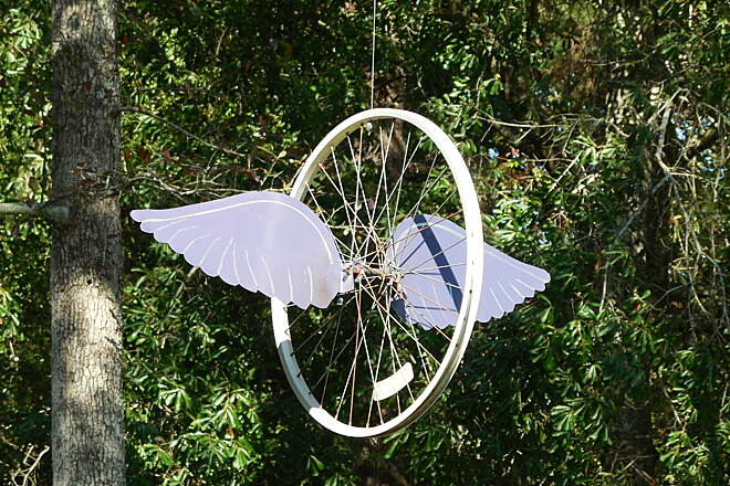 Mobile Airport Perimeter Trail Winged Wheel This has been hung on private property next to the trail.  It can only be seen by the residents of the property and those on the trail, so it is obviously for the enjoyment of the cyclists / walkers.
