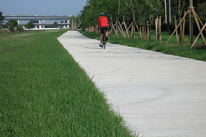 New River Greenway Riding west from SW 136th Street A lone rider heading west towards the flyover and Markham Park. The old State Road 84 trail still usable on the south side of the canal from 136th ST to Markham Park.