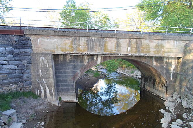 Northwest Lancaster County River Trail Northwest River Trail Railroad arch bridge across Conoy Creek south of Bainbridge. Notice the reflective quality of the water. Taken May 2015.