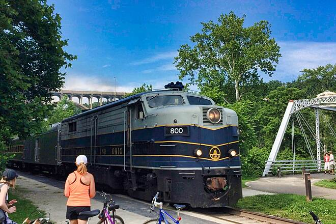 Ohio & Erie Canal Towpath Trail Anticipated Arrival The Bike Onboard passengers watch the arrival of the Cuyahoga Valley Scenic Railroad train at Brecksville Station.  Riders take the train in one direction and ride back to where they started.  July 3, 2015.