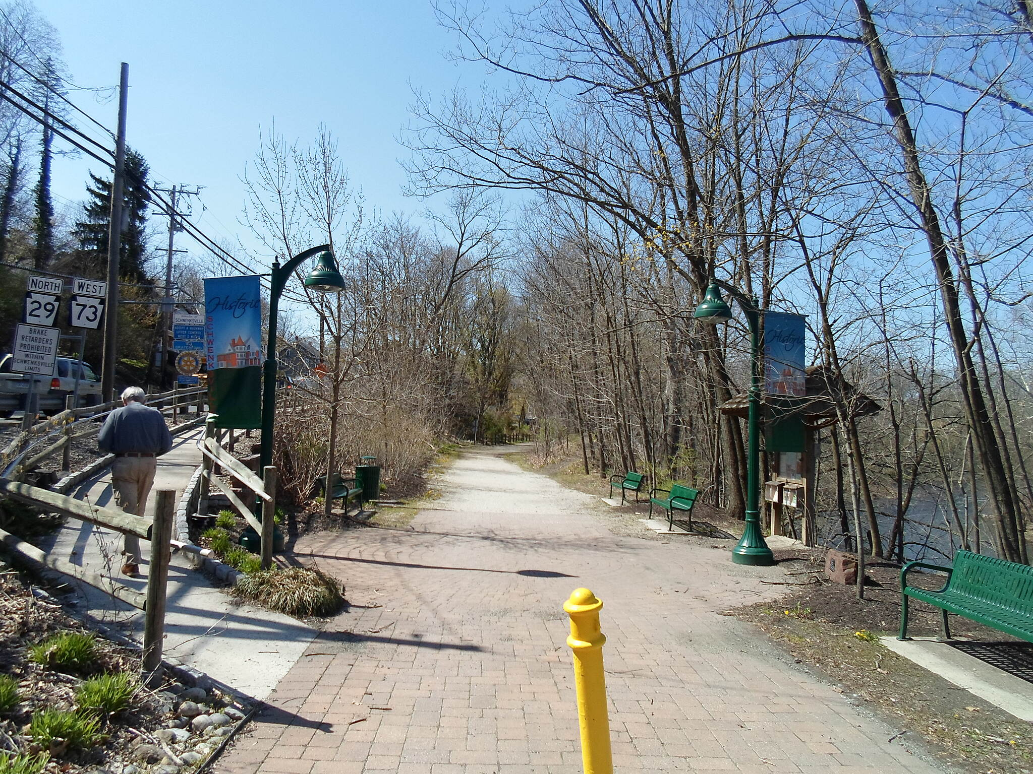 Perkiomen Trail Perkiomen Trail Looking north from the trail crossing at Route 73. The pocket park doubles as a junction between the trail and the sidewalk that follows Routes 29 and 73 into Schwenksville, which veers up the ramp to the left. Taken Apr. 2016.