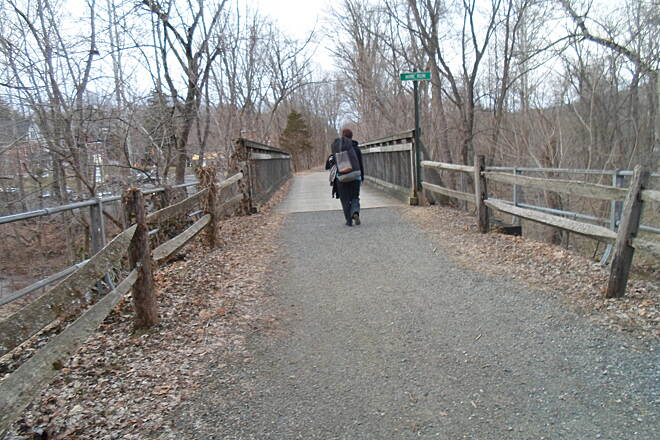 Perkiomen Trail Perkiomen Trail Woman crossing a restored railroad bridge in Schwenksville. The old railing from the days of the railroad can still be seen behind the newer, wooden ones built for the trail.
