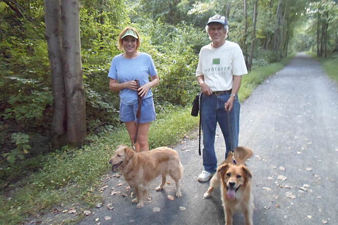 Schuylkill River Trail Bartram Trail Couple walking on the trail with their pet Golden Retrievers near the Warren Truss bridge on a balmy, late summer evening. Taken Aug. 2014.