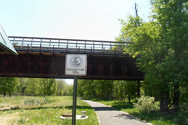 Skippack Trail Skippack Trail After branching from the Perkiomen Trail, the Skippack Trail passes under a restored RR trestle, then heads south through the woods. Taken May 2015.
