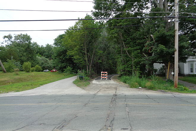 Southern New England Trunkline Trail View west at Central St,  View is west at Central St., Millville, MA on 7/18/15 of the newly paved SNETT. Note rails buried in the street in the foreground.
