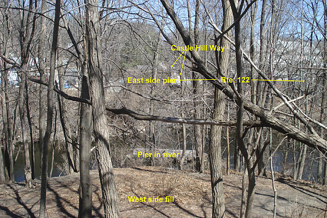 Southern New England Trunkline Trail Missing Blackstone bridge View east on 4/10/14 across Blackstone River in Blackstone, MA at site of missing bridge. View shows remains of pier in river, pier on east bank and Castle Hill Way.