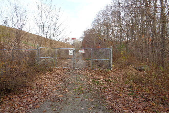 Southern New England Trunkline Trail View east Farm St., Blackstone View eastward at Farm St., Blackstone on 11/13/14. Fence is for the closed Woonsocket landfill on left. a narrow trail skirts fence on right.